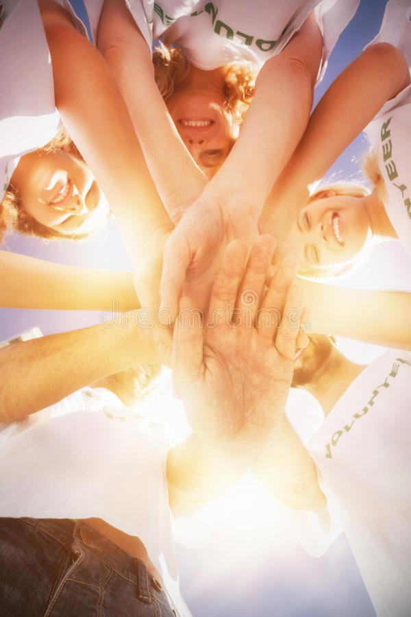 Lyckliga volontärer med händer tillsammans mot blå himmel arkivbild