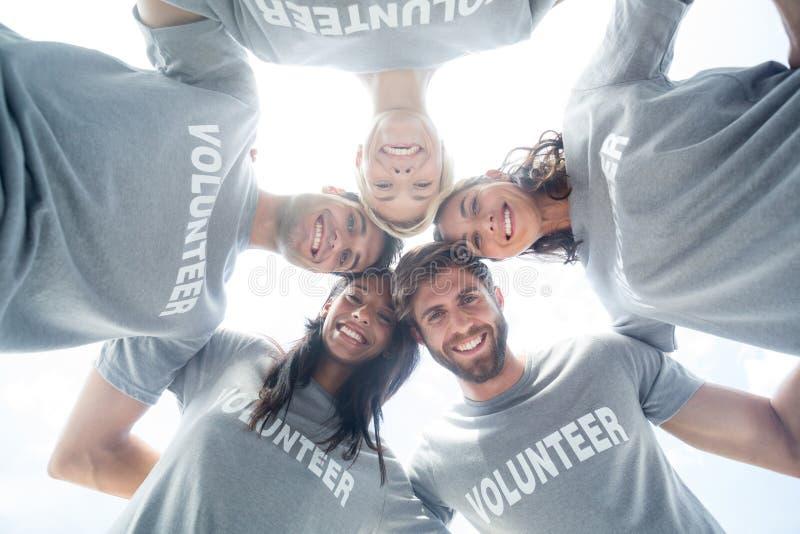Lyckliga volontärer som bildar bråteet arkivfoto
