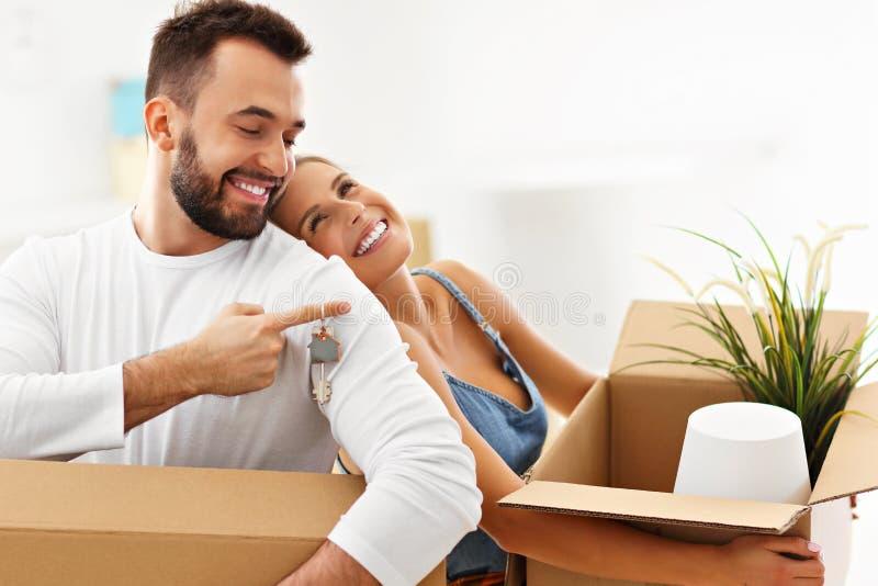 Lyckliga vuxna par som är rörande ut eller in till det nya hemmet arkivbilder