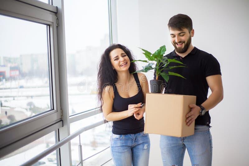 Lyckliga vuxna par som är rörande ut eller in till det nya hemmet royaltyfri bild