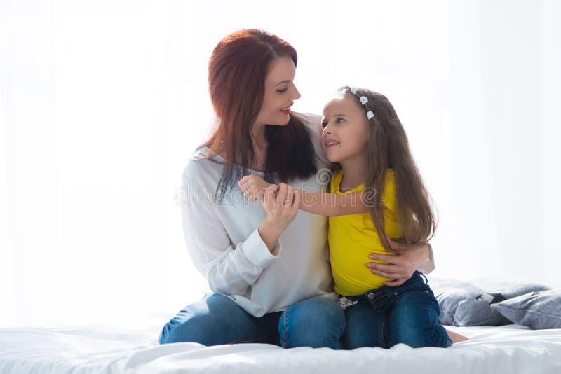 lyckligt älska för familj Fostra och hennes dotterbarnflicka som spelar och kramar arkivbilder
