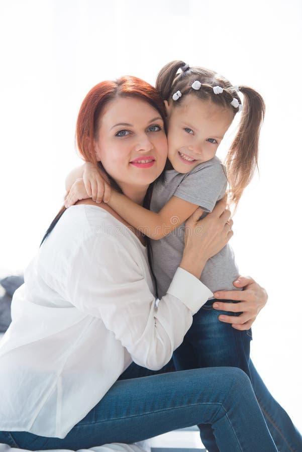 lyckligt älska för familj Fostra och hennes dotterbarnflicka som spelar och kramar royaltyfria bilder