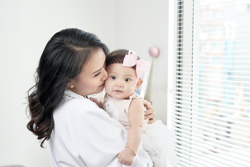 lyckligt älska för familj modern som spelar med henne, behandla som ett barn i sovrummet arkivbild