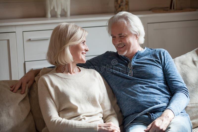 Lyckligt älska talande koppla av för höga par på soffan tillsammans arkivbild