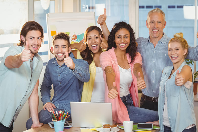 Lyckligt affärsfolk med teknologier som visar upp tummar royaltyfri foto