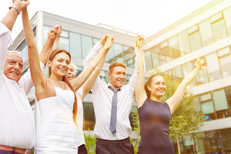 Lyckligt affärsfolk som rymmer upp deras armar royaltyfri bild