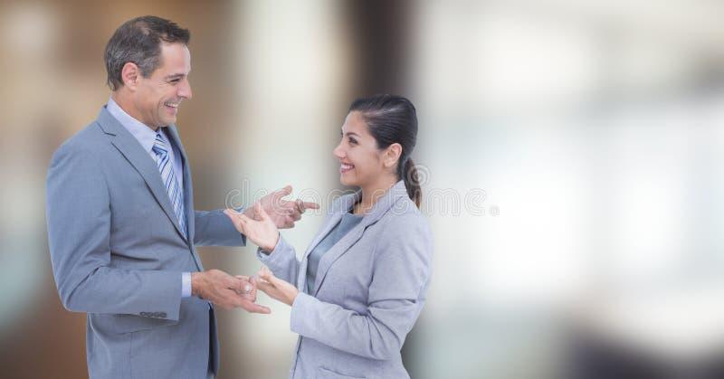 Lyckligt affärsfolk som talar mot suddig bakgrund royaltyfria foton