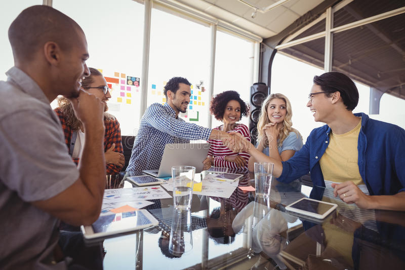 Lyckligt affärslag som tillsammans arbetar på kontoret arkivbilder