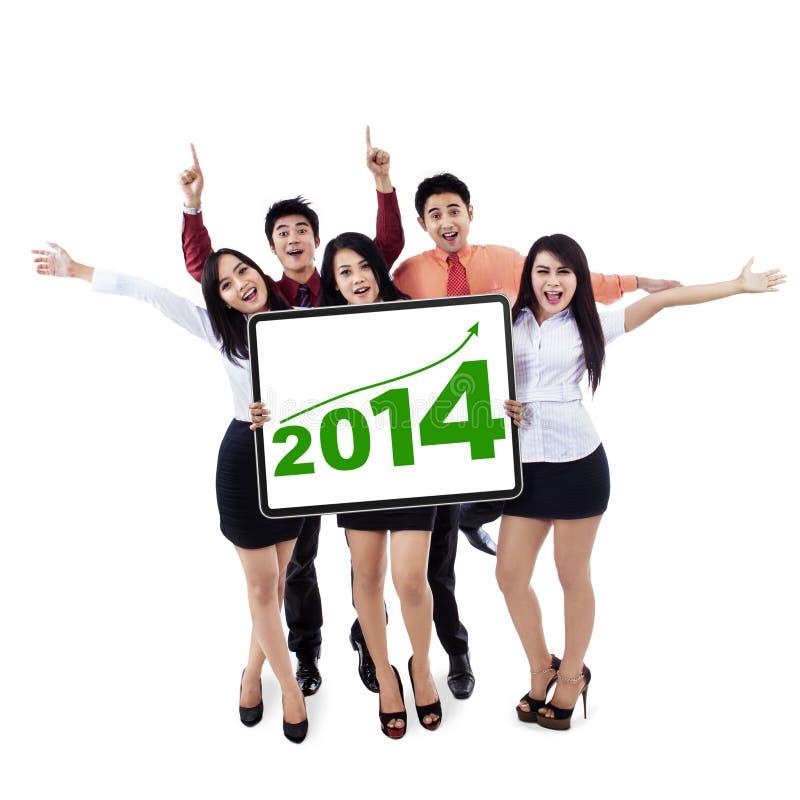 Lyckligt affärslag som visar det nya året 2014 royaltyfria foton