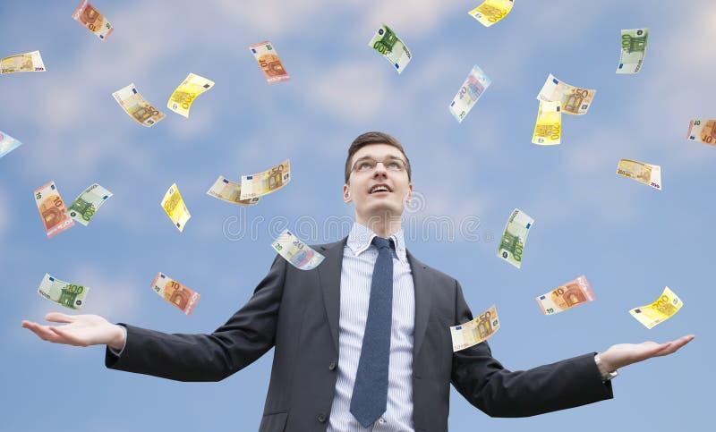 Lyckligt affärsmananseende i regnet av pengar arkivfoto