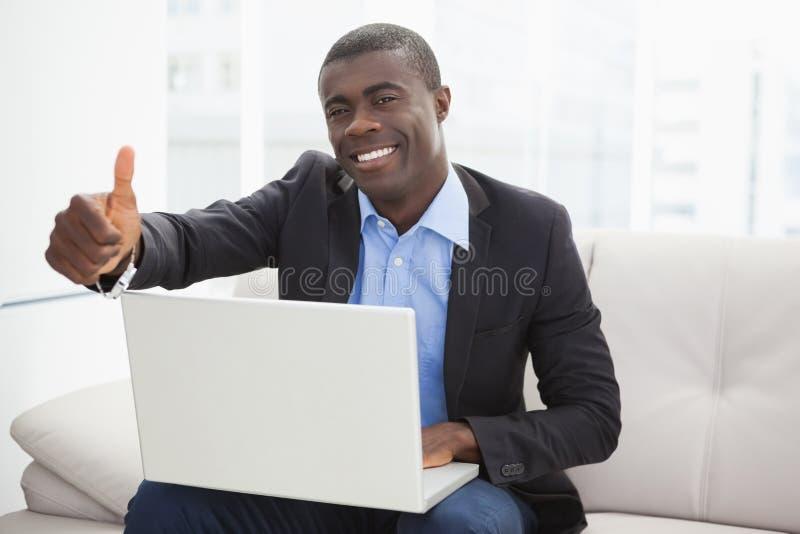 Lyckligt affärsmansammanträde på soffan med bärbar datorvisning tummar upp arkivfoto