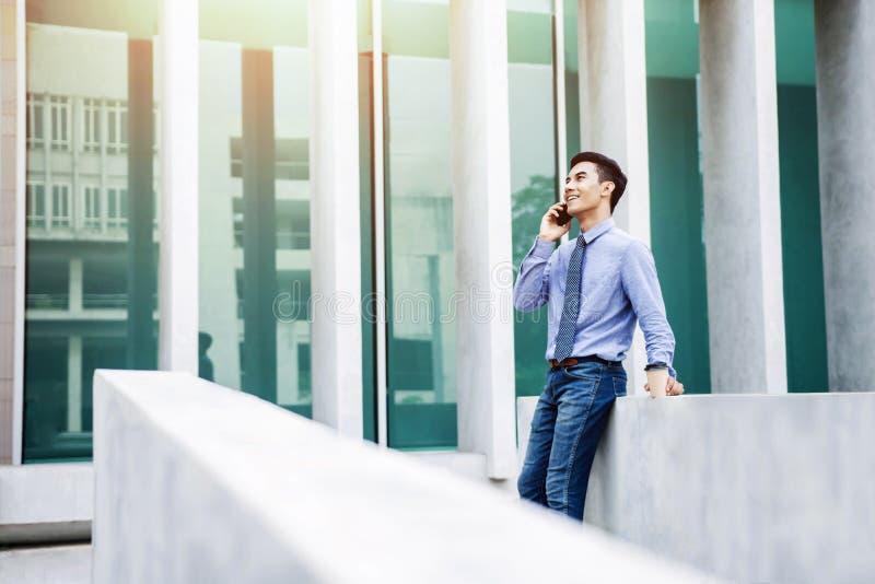 Lyckligt affärsmansamtal via utvändig kontorsbyggnad för smart telefon royaltyfri foto