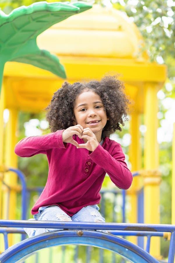 Lyckligt afrikansk amerikanbarn som spelar i en parkera royaltyfri fotografi