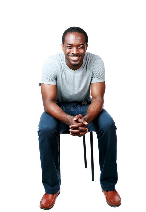 Lyckligt afrikanskt mansammanträde på stolen royaltyfria bilder