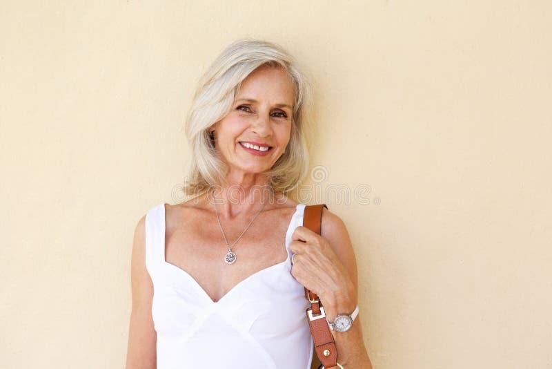 Lyckligt anseende för äldre kvinna i vårklänning med handväskan arkivbild