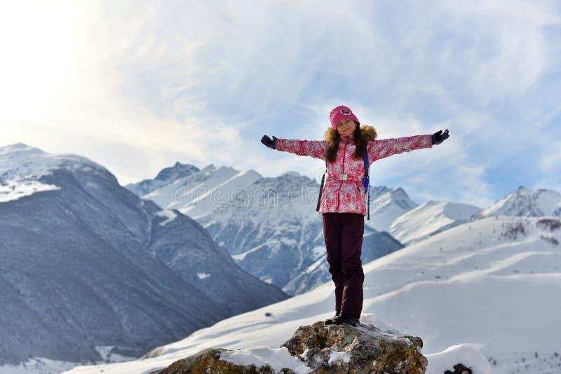 Lyckligt anseende för tonårs- flicka på en sten som ler i snöig berg arkivfoto