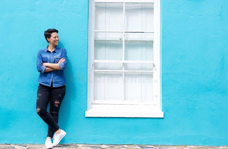Lyckligt anseende för ung kvinna bredvid fönster royaltyfri bild