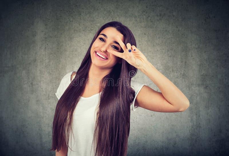 Lyckligt anseende för ung kvinna som ger en fredgest arkivbilder