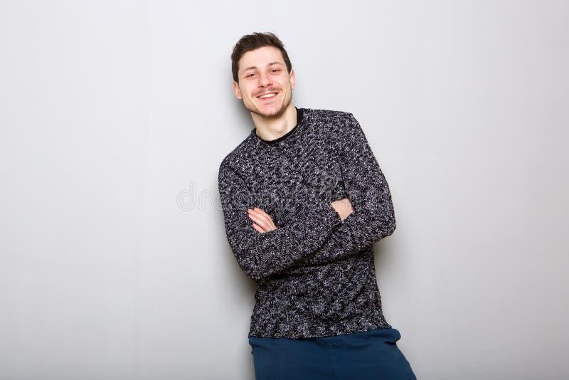Lyckligt anseende för ung man mot den gråa väggen royaltyfria bilder