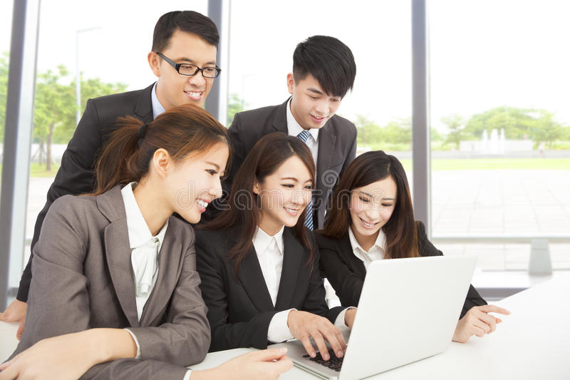 Lyckligt asiatiskt affärslag som i regeringsställning arbetar arkivfoton