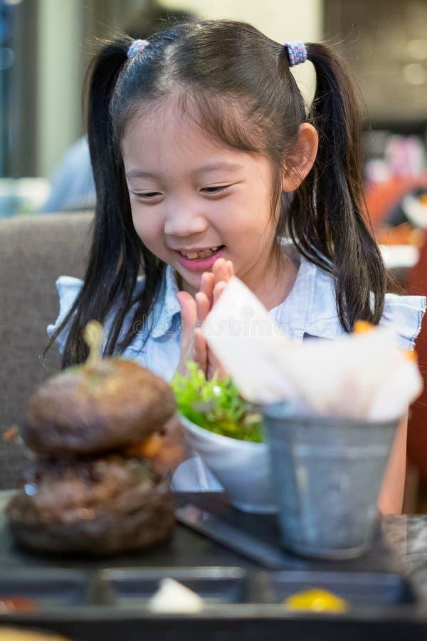 Lyckligt asiatiskt barn, flicka som är upphetsad med hamburgaren royaltyfria foton