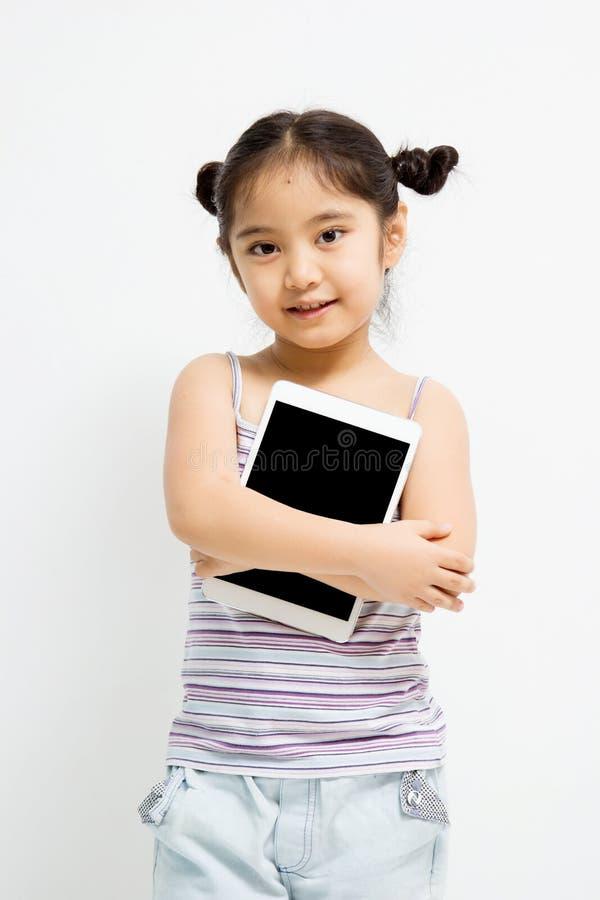 Lyckligt asiatiskt barn med minnestavladatoren royaltyfri fotografi