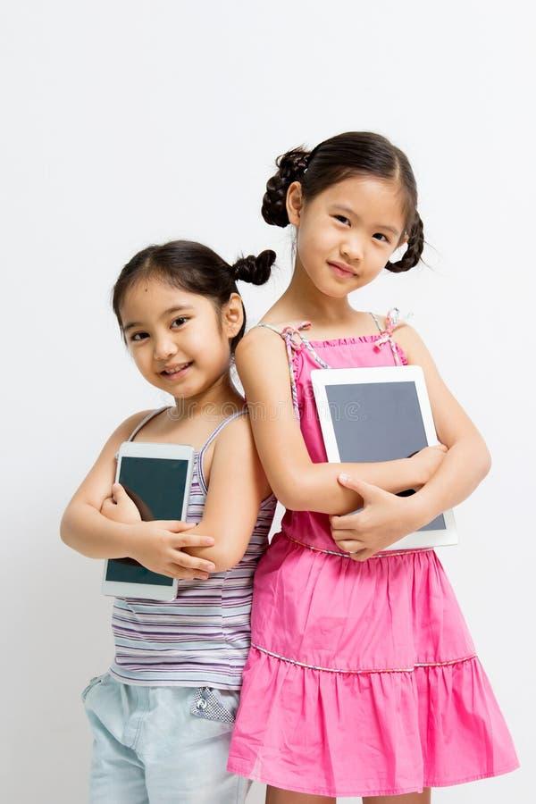 Lyckligt asiatiskt barn med minnestavladatoren royaltyfri bild