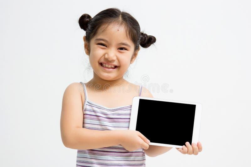 Lyckligt asiatiskt barn med minnestavladatoren royaltyfria foton