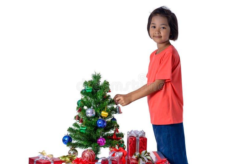 Lyckligt asiatiskt barn som rymmer den lilla klockan för garneringjulgran- och gåvaaskar  arkivbilder