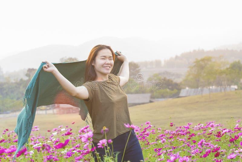 Lyckligt asiatiskt kvinnadamanseende på handen för löneförhöjning för kosmosblommafält upp med den lycklig och för frihetsframsid royaltyfri fotografi