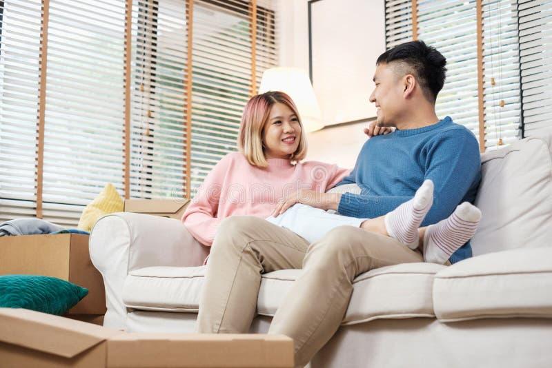 Lyckligt asiatiskt parsammanträde på soffan, når uppackning av kartongen fotografering för bildbyråer