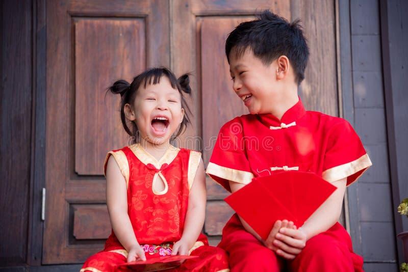 Lyckligt asiatiskt syskon i kinesisk traditionell dräkt royaltyfri bild