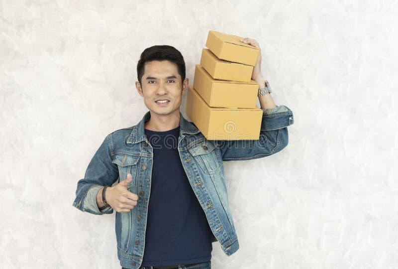 Lyckligt asiatiskt ungt anseende för leveransman med asken för jordlottstolpe på vit bakgrund royaltyfri bild