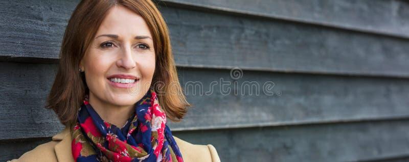 Lyckligt attraktivt mellersta åldrigt baner för kvinnapanoramarengöringsduk royaltyfri bild