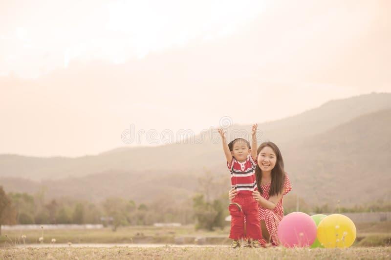 Lyckligt av modern och sonen som utomhus spelar på solnedgången arkivfoto