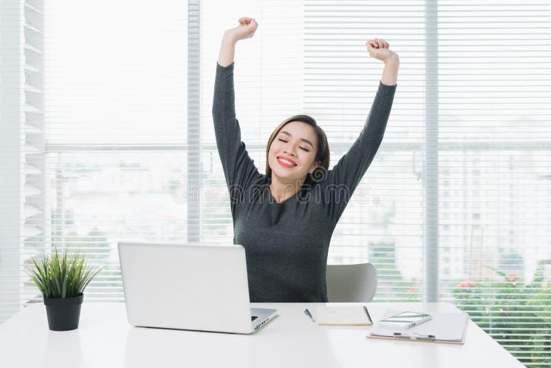 Lyckligt avkopplat sammanträde för ung kvinna på hennes skrivbord med en bärbar dator, str arkivfoton