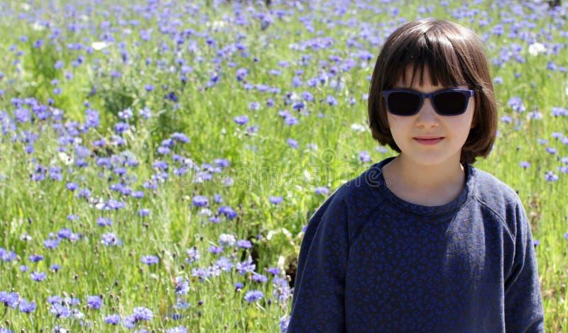Lyckligt barn över en blom- fältbakgrund för solig lantlig blåklint royaltyfri bild
