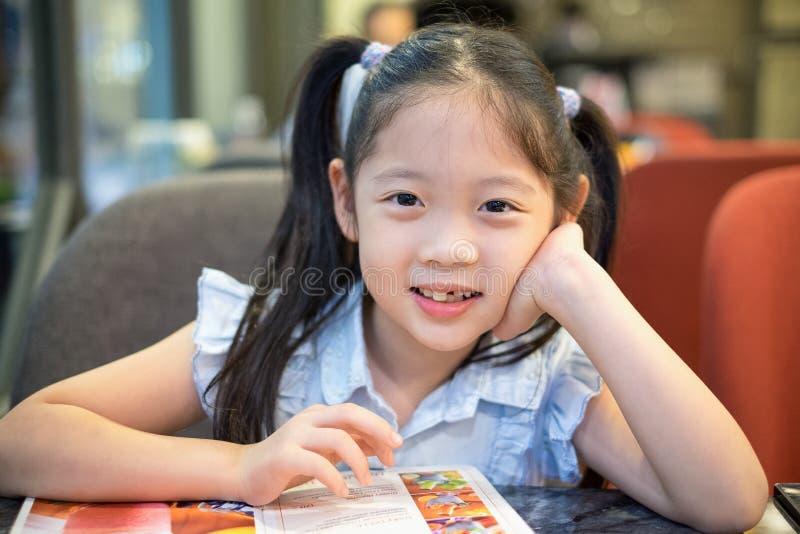 Lyckligt barn, flicka och att sitta på restaurangen och leendet royaltyfri foto