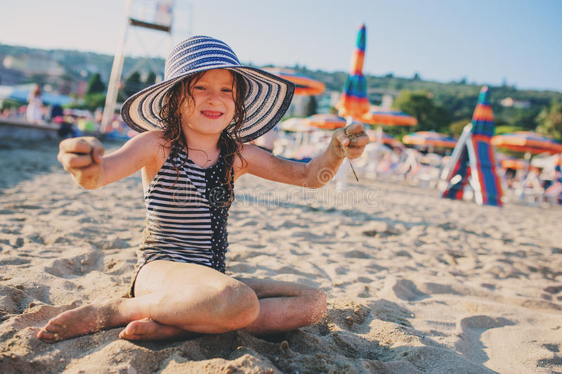 Lyckligt barn i baddräkt som kopplar av på sommarstranden och spelar med sand Värme väder, hemtrevligt lynne royaltyfria foton