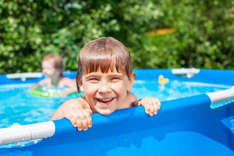 Lyckligt barn i en simbassäng utomhus fotografering för bildbyråer