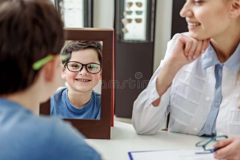 Lyckligt barn i eyewear som kastar en blick i spegel fotografering för bildbyråer