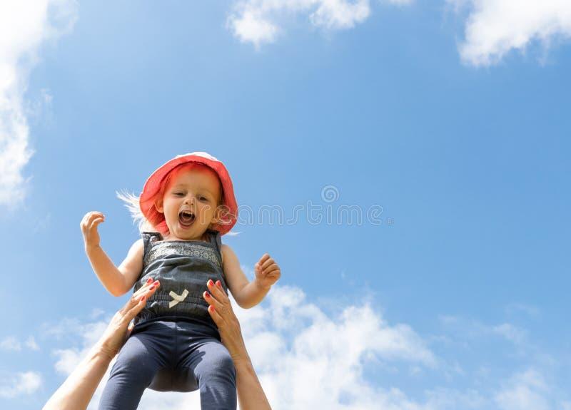 Lyckligt barn i himlen sommar f?r sn?ckskal f?r sand f?r bakgrundsbegreppsram Barndom f?r?ldraskap royaltyfri bild