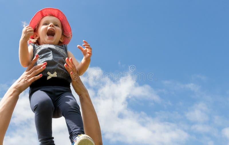 Lyckligt barn i himlen sommar f?r sn?ckskal f?r sand f?r bakgrundsbegreppsram Barndom f?r?ldraskap royaltyfri fotografi