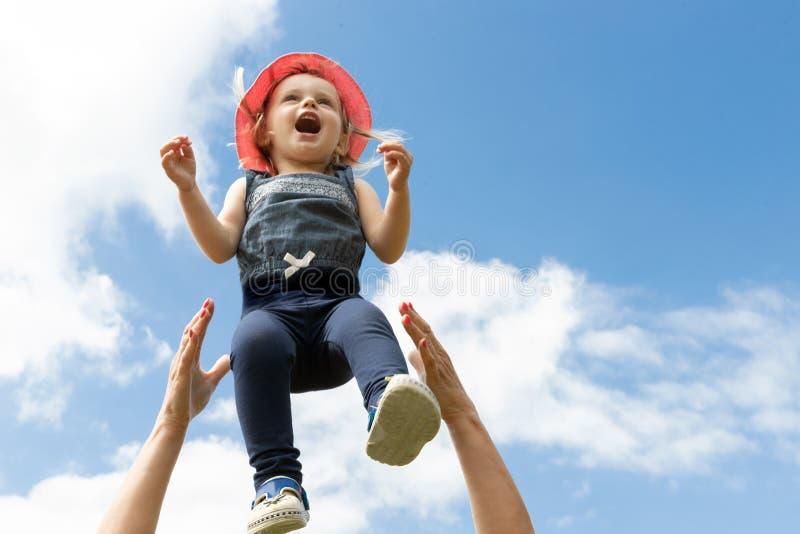 Lyckligt barn i himlen sommar f?r sn?ckskal f?r sand f?r bakgrundsbegreppsram Barndom f?r?ldraskap arkivfoto