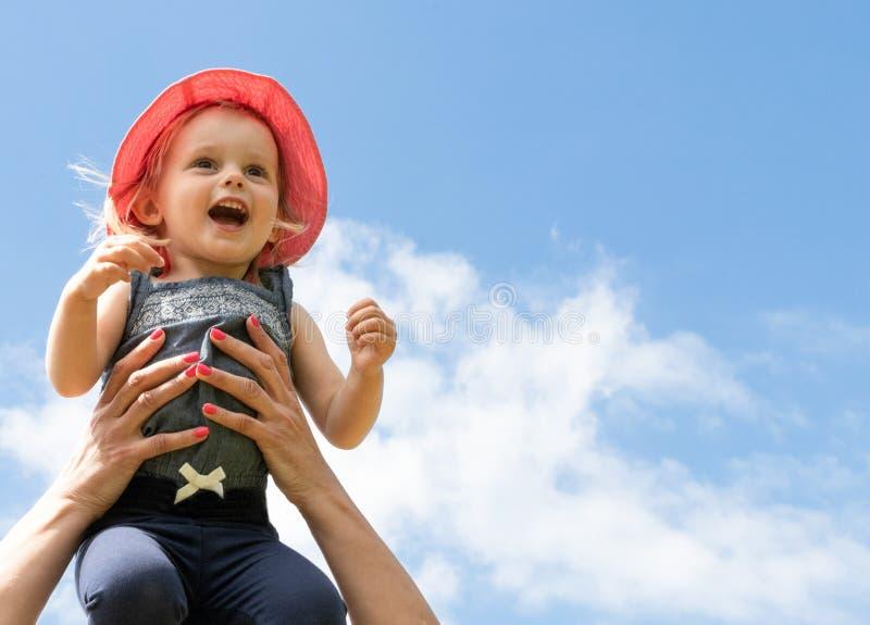 Lyckligt barn i himlen sommar f?r sn?ckskal f?r sand f?r bakgrundsbegreppsram Barndom f?r?ldraskap arkivbild