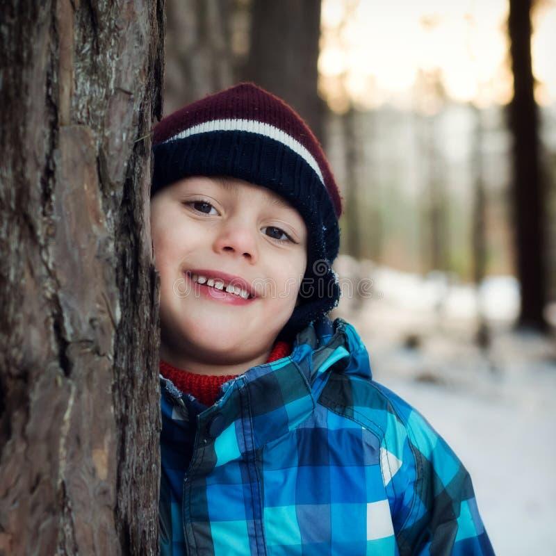 Lyckligt barn i vinterskog arkivfoto
