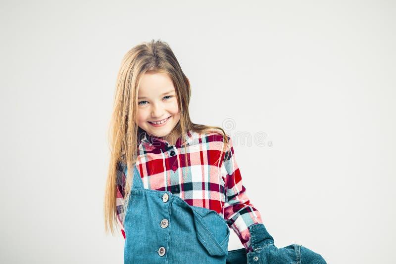 lyckligt barn lilla flickan ler glatt ungar danar i ett grov bomullstvillomslag och en muff skjorta Gr? f?rgbakgrund studio arkivfoton
