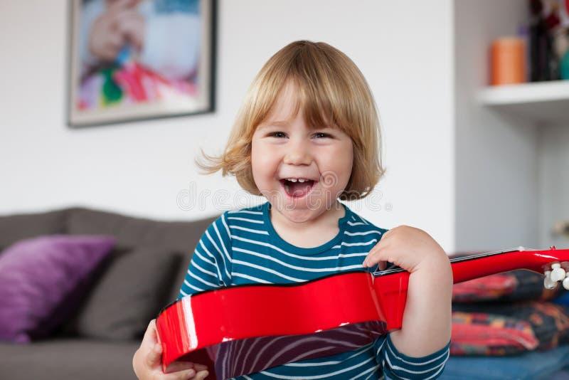 Lyckligt barn med den röda gitarren royaltyfri foto
