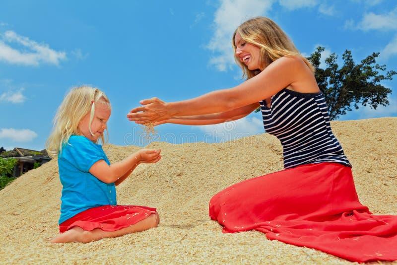 Lyckligt barn med modern på hög av riskornskörden royaltyfri foto