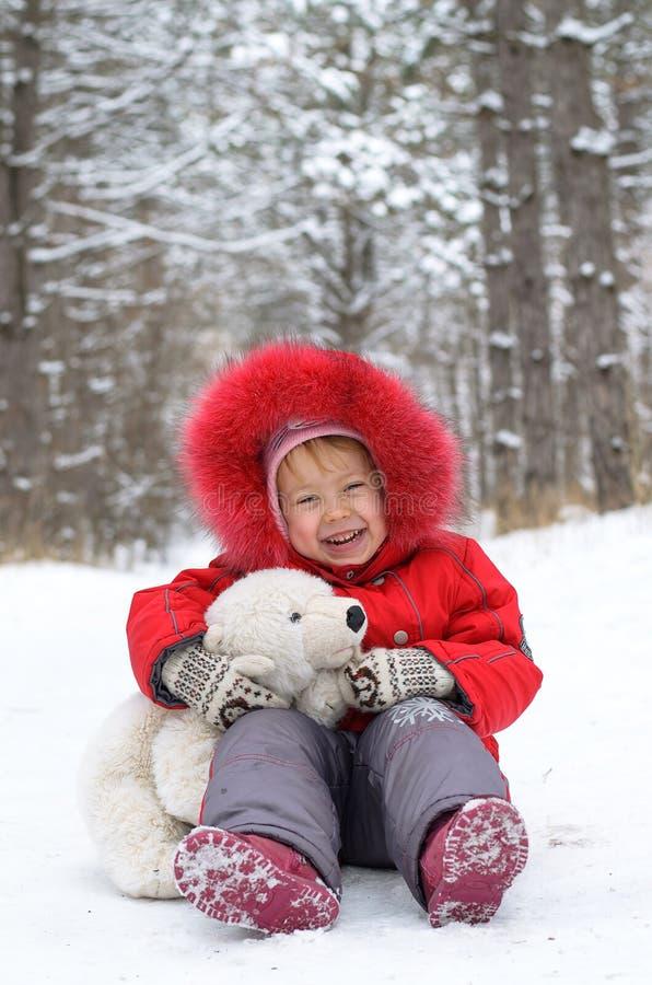 Lyckligt barn med nallebjörnen i snön royaltyfria bilder